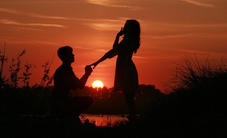 בן זוג כורע ברך מול בת זוגתו וברקע שקיעה