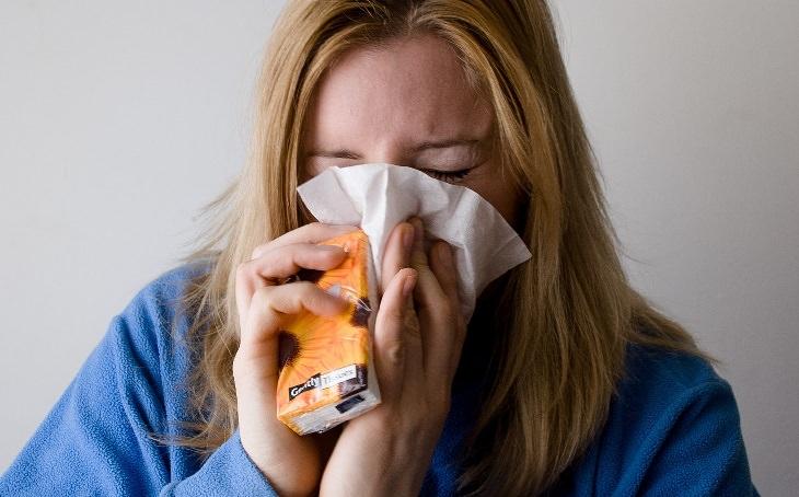 נקודות לחיצה לטיפול טבעי באף סתום: אישה מקנחת את האף