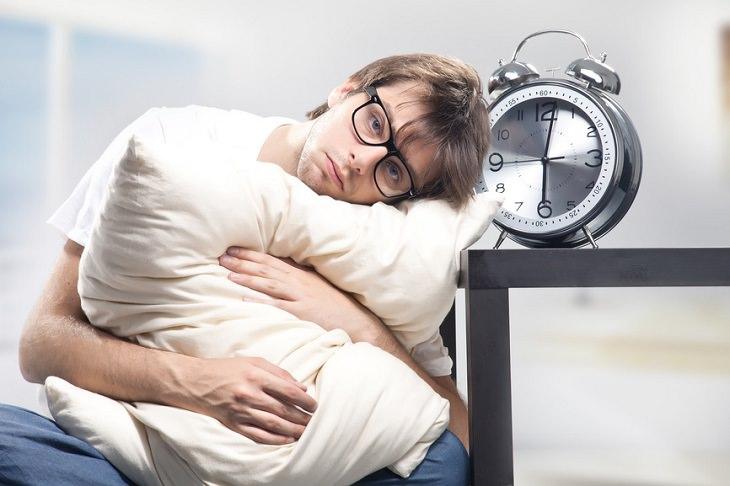 איש עצוב נשען על כרית על יד שעון מעורר