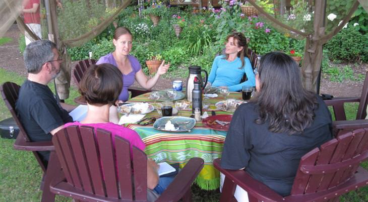 אנשים מדברים סביב שולחן אוכל עגול מחוץ לבית