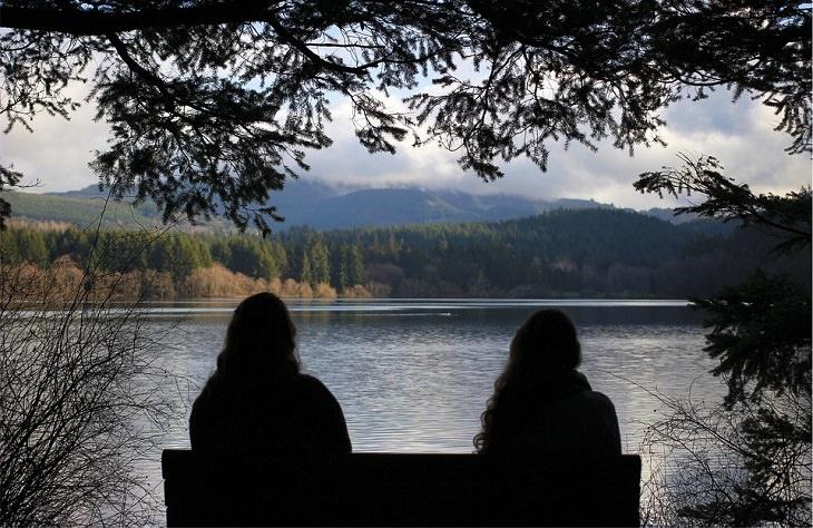 שתי נשים יושבות רחוקות אחד מן השניה על ספסל