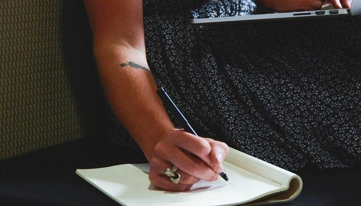 יד של אישה שכותבת במחברת