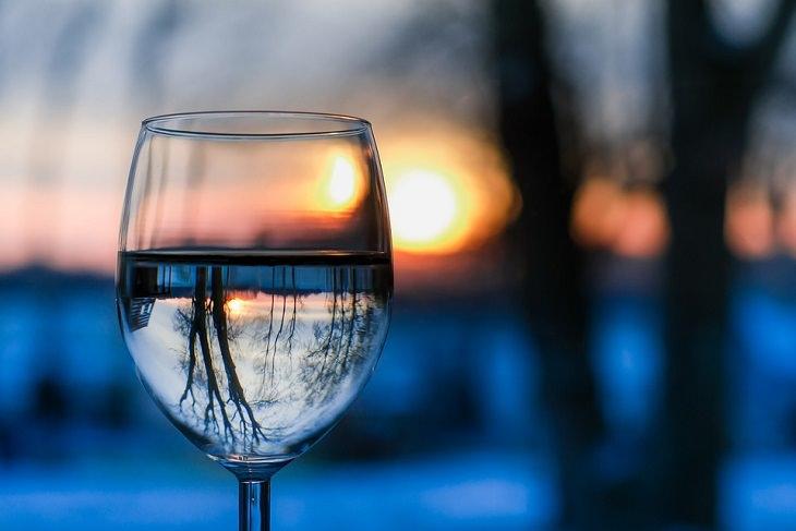 כוס מים וברקע נוף של אגם
