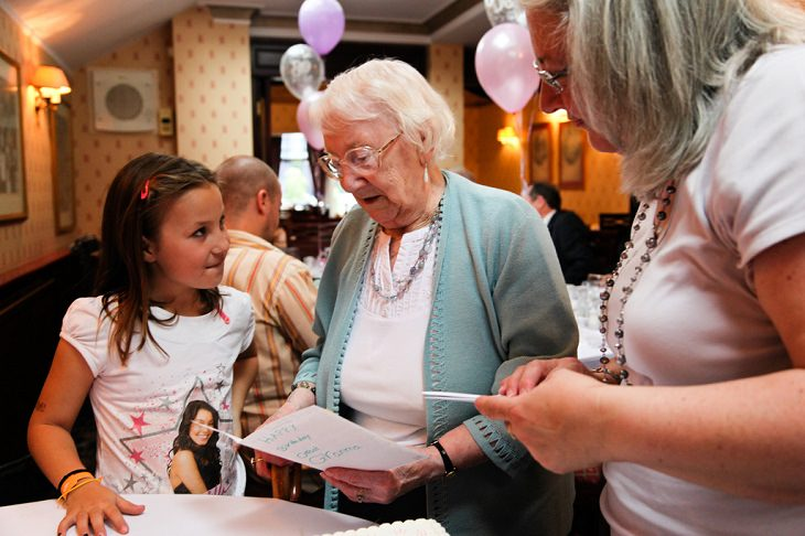 סבתא קוראת ברכת יום הולדת על יד הנכדה שלה
