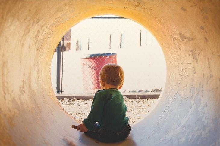 ילד יושב במגרש משחקים