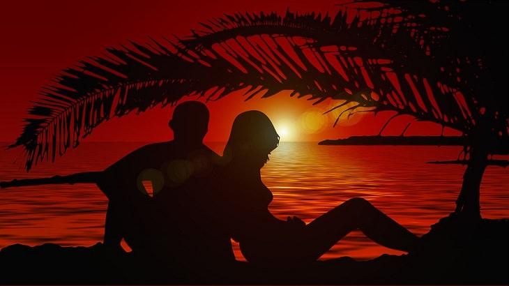 זוג שוכב על החוף לאור השקיעה