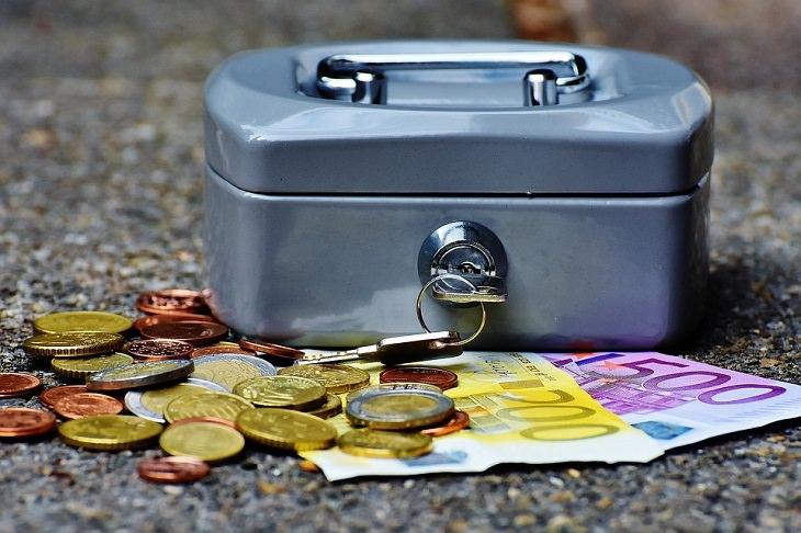 תיבה כסופה עם מפתח במנעול מונחת על שטרות של כסף
