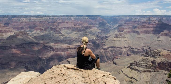 אישה יושבת על צוק ומביטה לעבר נוף מדברי
