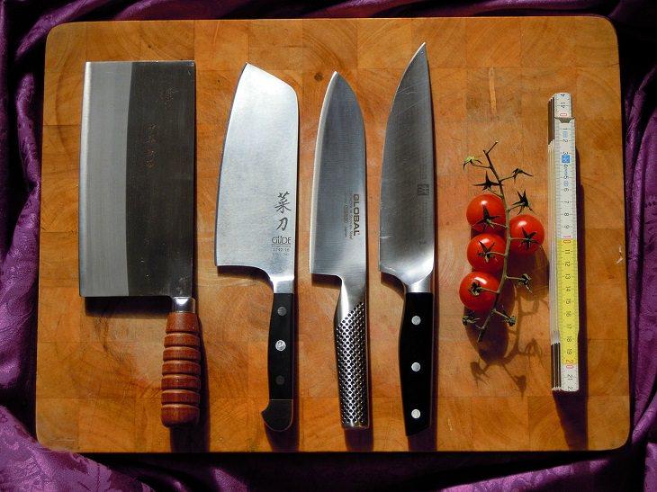 פריטים שמומלץ לא להכניס למדיח: סכיני שף מונחות על קרש עץ