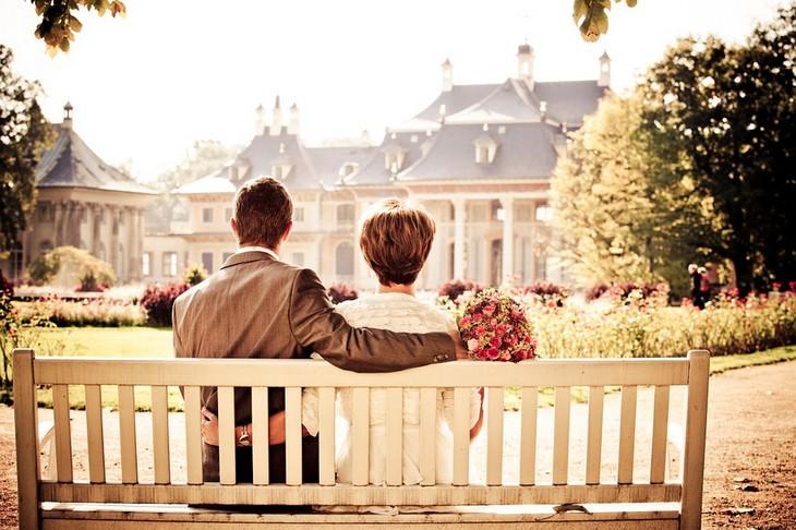 צילום גב של זוג יושב על ספסל