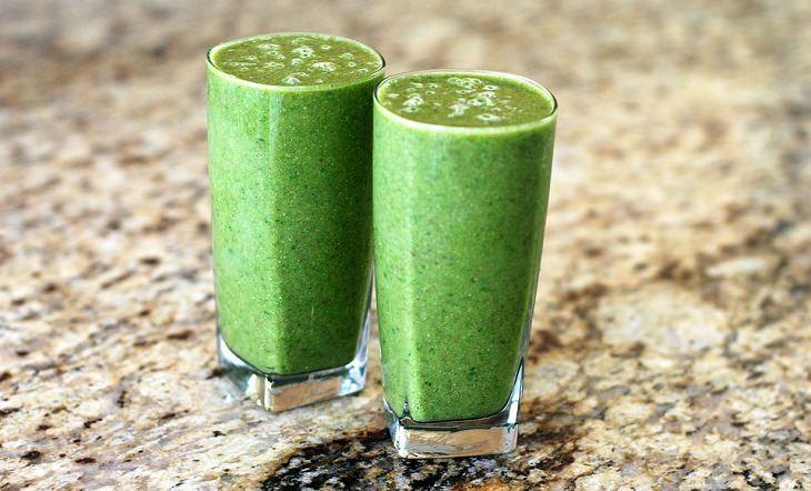 שתי כוסות זכוכית שקופות עם שייק ירקרק המורכב ממלפפון, חסה ותפוח