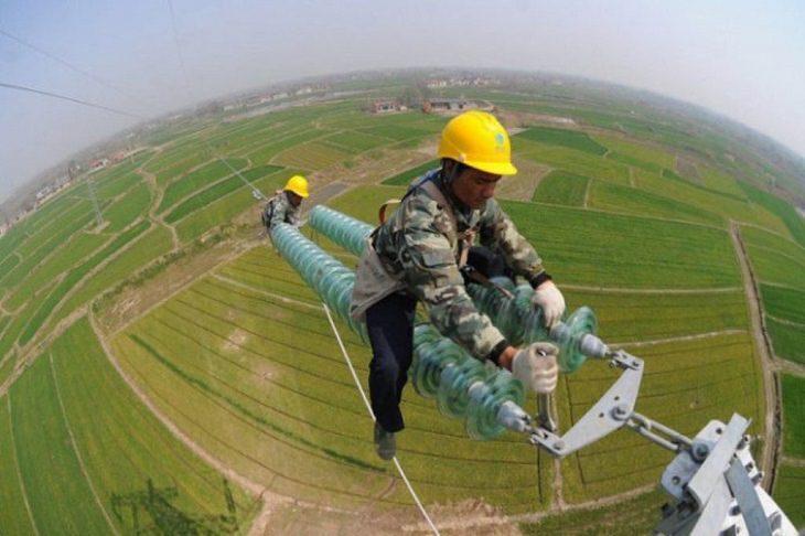 טכנאי יושב על עמוד חשמל גבוה