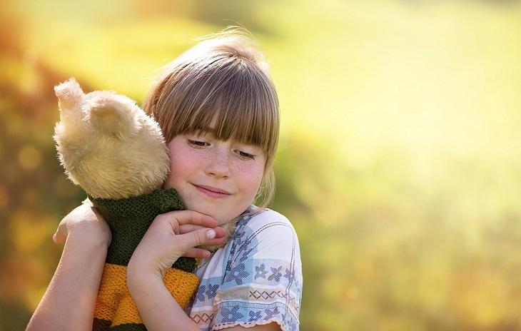 ילדה מחבקת בובת דובי