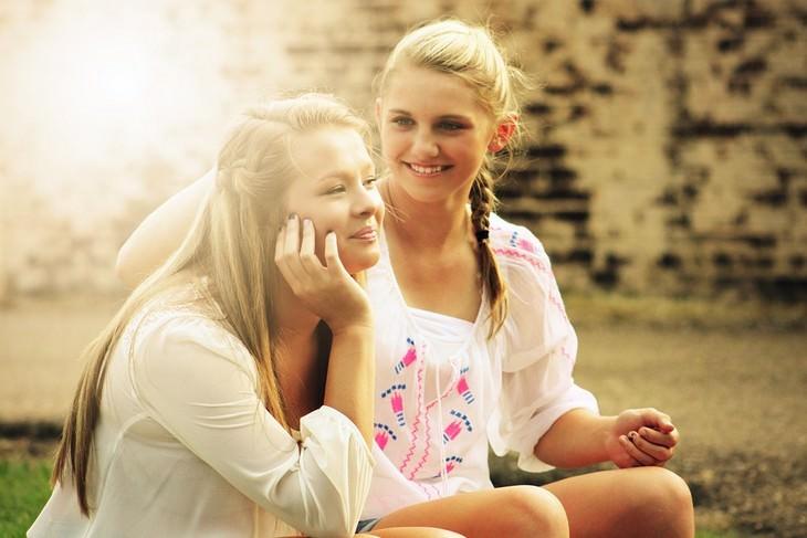 שתי נערות מחויכות יושבות זו לצד זו