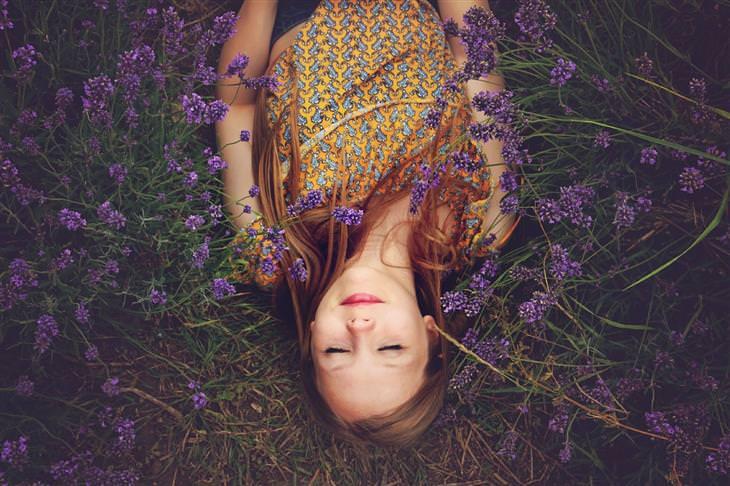 אישה שוכבת בשדה עם פרחים סגולים