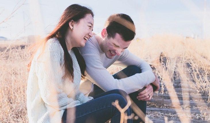 זוג יושבים בשדה יחדיו וצוחקים