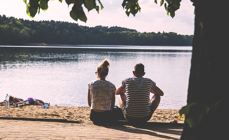 זוג יושבים תחת עץ ומשקיפים אל עבר אגם