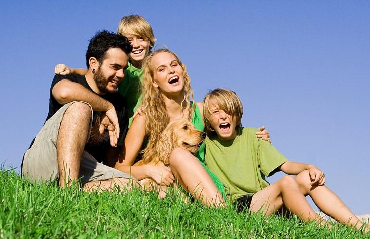 משפחה יושבת על הדשא וצוחקת יחדיו