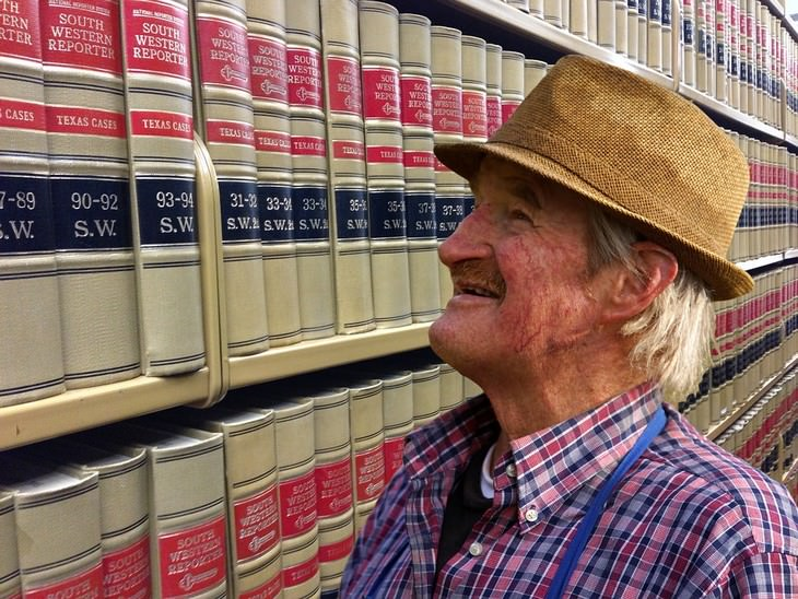 איש מבוגר מחייך מול ספרים
