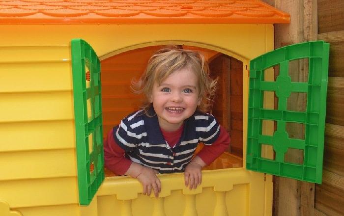 לגדל ילד חברותי: פעוט מביט החוצה מתוך חלון של בית צעצוע