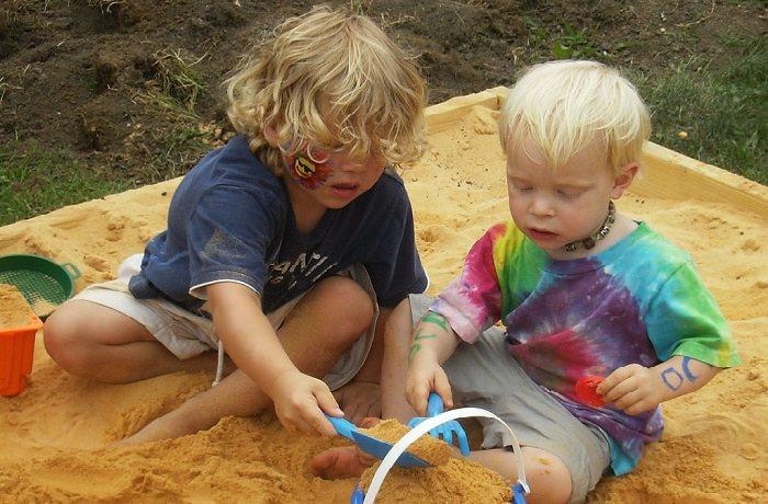לגדל ילד חברותי: שני ילדים משחקים בארגז חול