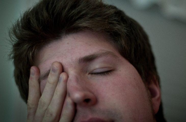 סיבות לעייפות מתמדת: איש מעביר את ידו על פניו ועוצם את עיניו