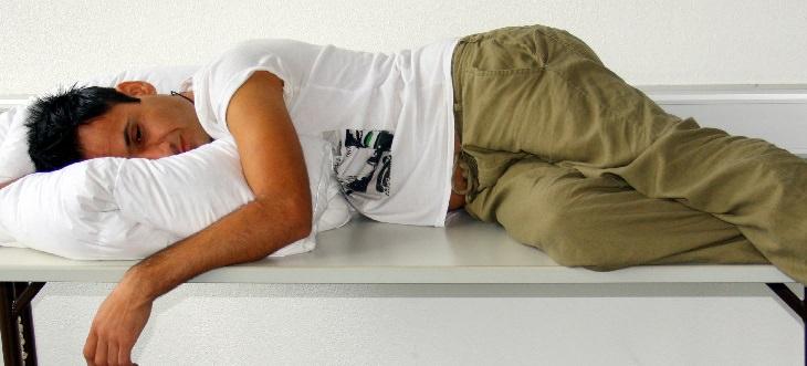 סיבות לעייפות מתמדת: איש מנסה לישון על שולחן עם כרית, ולבוש בבגדי יומיום