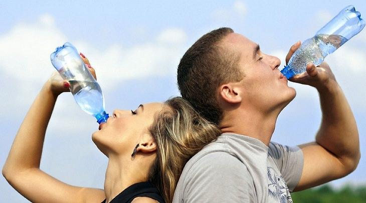 היתרונות הבריאותיים של שתיית מים: בחור ובחורה שותים מים מבקבוק