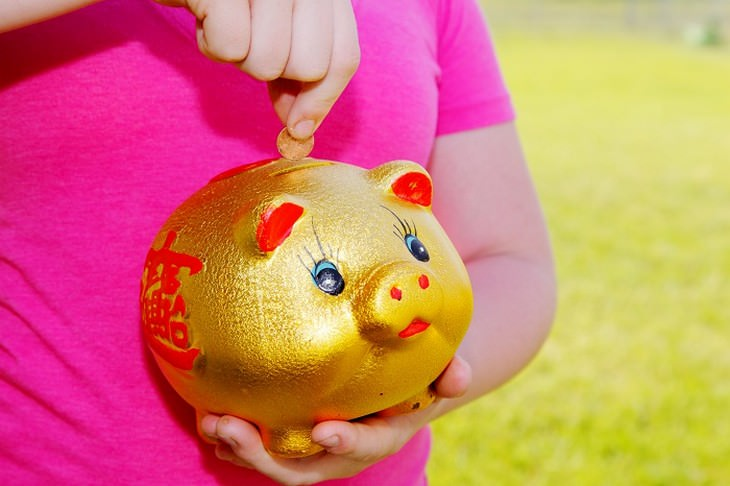 משפטים שהורים לא צריכים להגיד: ילדה מכניסה מטבע לקופת חיסכון בצורת חזיר