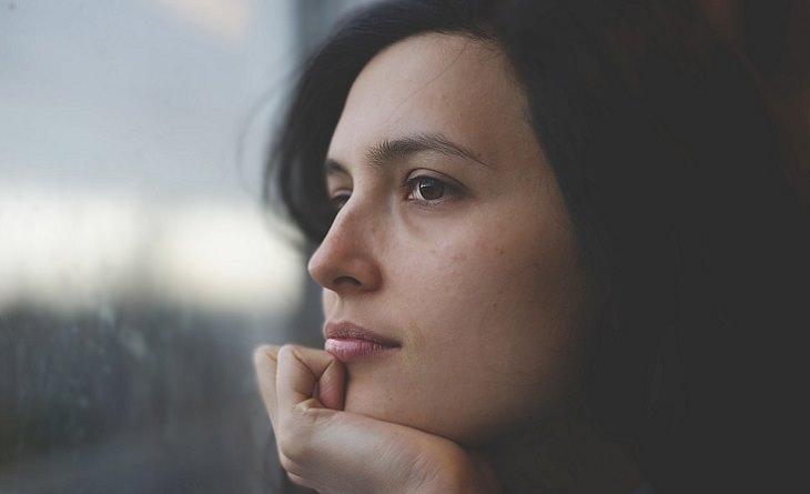 אישה מהורהרת נשענת על ידה מול חלון
