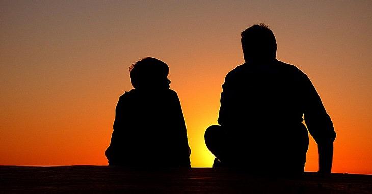 50 חוקי זהב להורות נכונה: אב ובן על רקע השקיעה