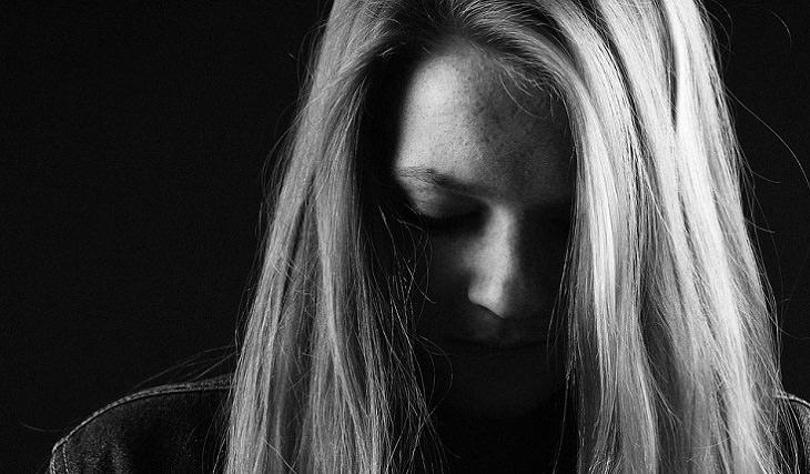 בריאות המעיים: אישה מרכינה את ראשה בעצב