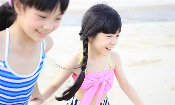 הורות מזיקה: שתי ילדות רצות על חוף הים