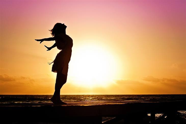 דרכים להפחתת לחץ: צללית של אישה מרימה את ראשה לשמים מול השקיעה