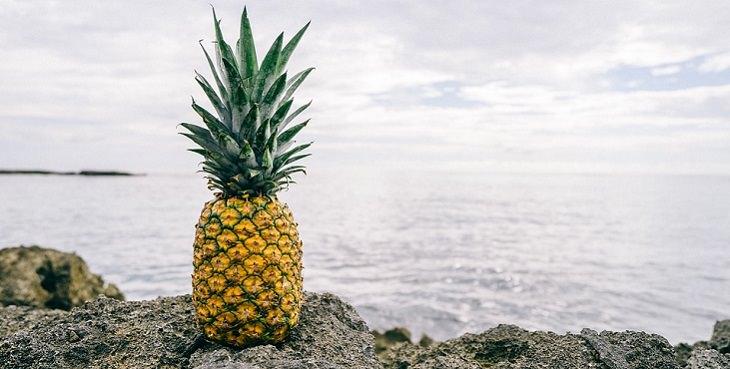 היתרונות הבריאותיים של משקה אננס: אננס מונח על גבי סלע מול הים