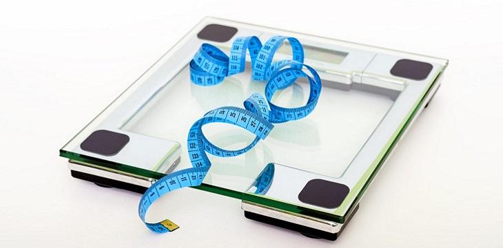 היתרונות הבריאותיים של משקה אננס: משקל אלקטרוני עם סרט מדידה עליו