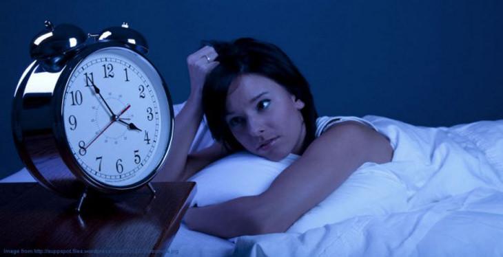 מיצים טבעיים לשיפור השינה: אישה מיטה מביטה על שעון