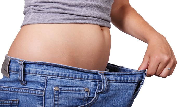 יתרונות האספרגוס: אישה אוחזת בשולי מכנסיים שגדולים על מידותיה