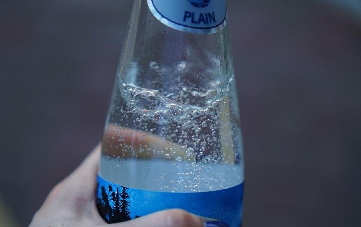 שימושים בסודה לשתייה בבישול: יד אוחזת בבקבוק של מים מוגזים
