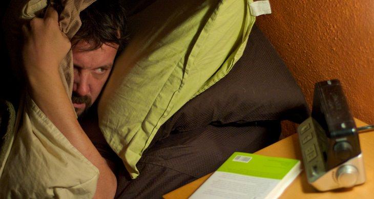 מדיטציית המודעות: איש מסתכל על השעון בזמן שהוא מנסה לישון