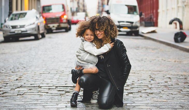 טיפים מדעיים לגידול ילדים מצליחים: אימא מחבקת את בתה ברחוב