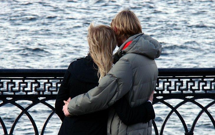 סימנים לזוגיות יציבה וחזקה: זוג עומד על גשר ומסתכל לעבר הים