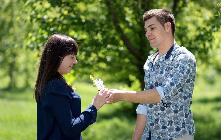 סימנים לזוגיות יציבה וחזקה: גבר מושיט פרח לבת זוגתו