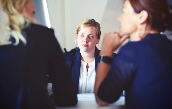 עצות שעוזרות להפסיק לקחת דברים באופן אישי: אישה מביטה בשתי נשים אחרות