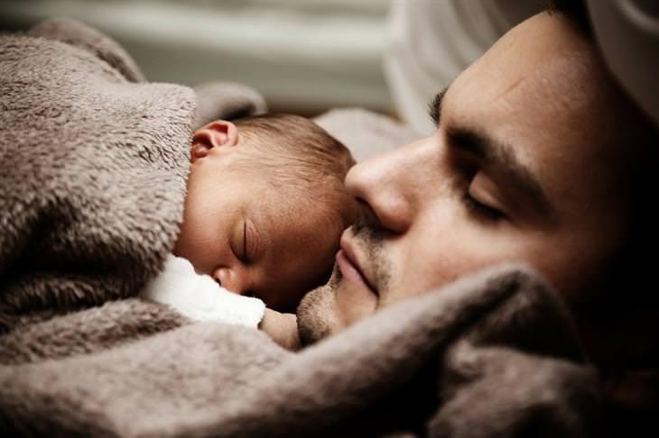 אבא ישן עם תינוק עליו