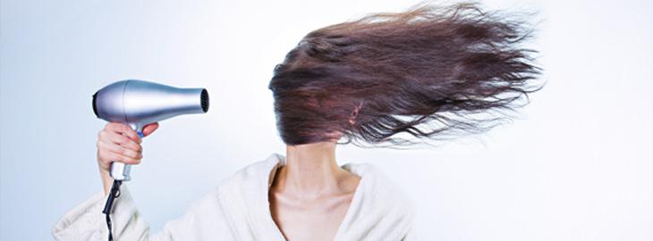 חומרי ניקוי מפתיעים בבית: אישה משמתשת בפן שמעיף הצידה את שיערה