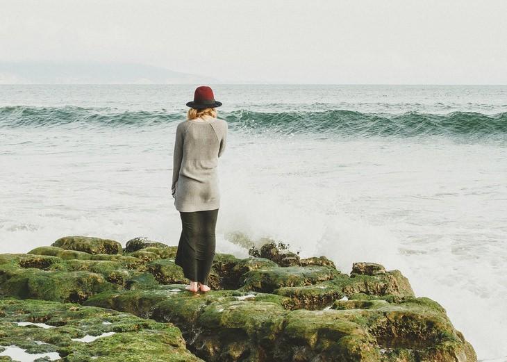 אישה עומדת על סלע ומסתכלת על הים
