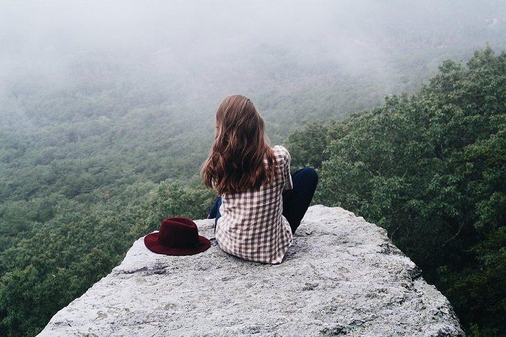 אישה יושבת ישיבה מזרחית מול צוק ונהנית מהנוף
