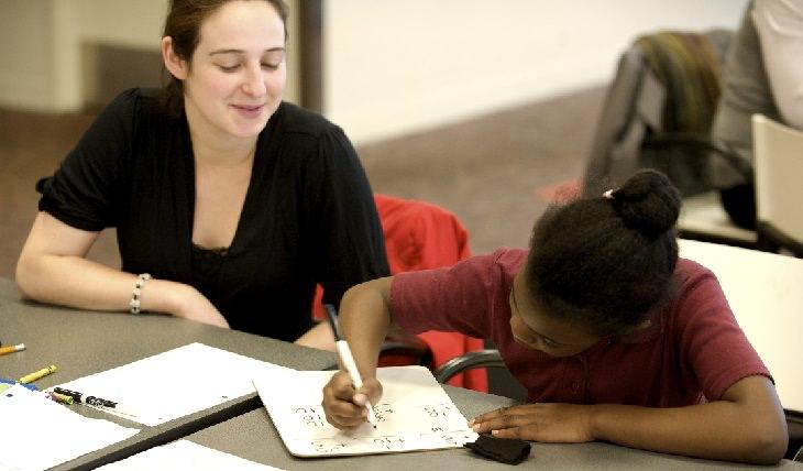 מורה יושבת ליד ילדה שעושה שיעורים