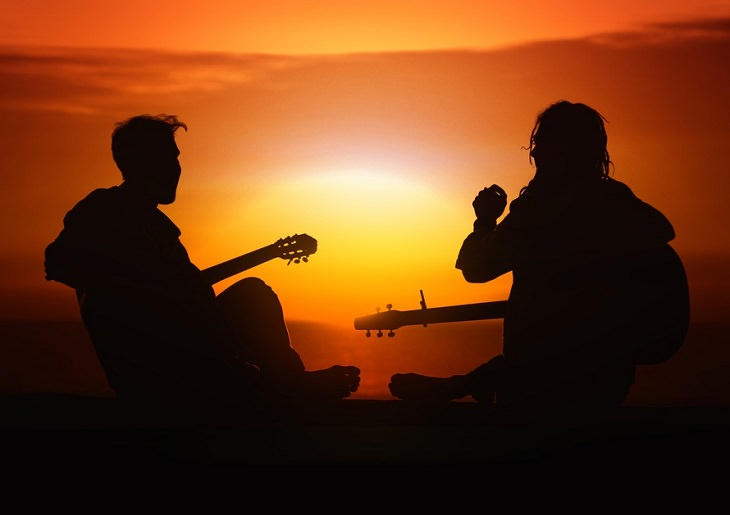 שני אנשים מנגנים על גיטרה מול שקיעה